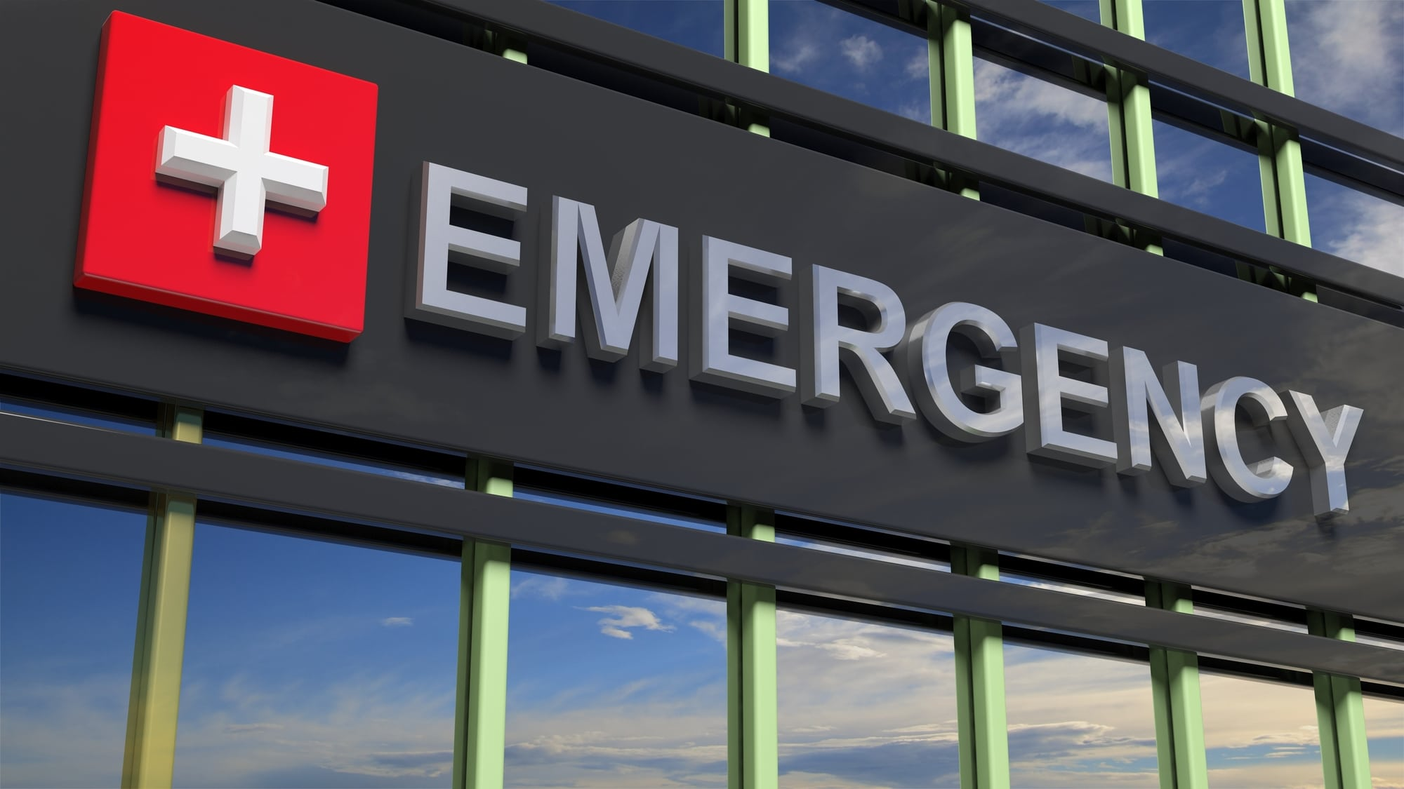 Emergency department building sign closeup, with sky reflecting in the glass.