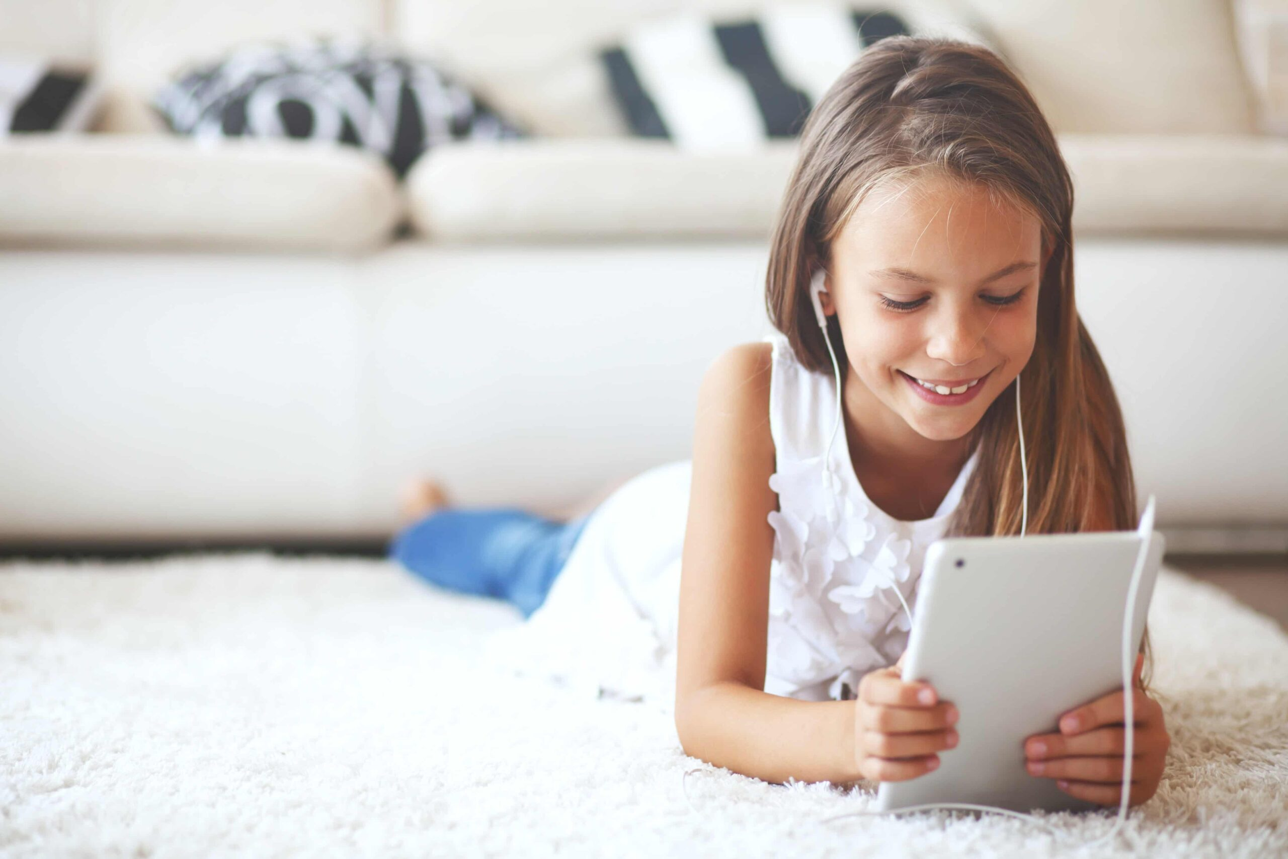 Child looks at iPad with earbuds